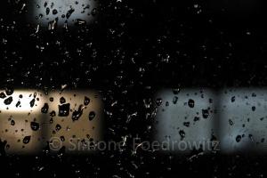 beleuchtete Fenster hinter einer Glasscheibe mit Regentropfen