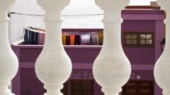 Hinter einer weißen Balustrade hängt Wäsche auf dem Dach eines lilafarbenen Haus