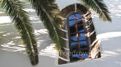 Kirchenfenster mit weißer Wand und Palmwedel