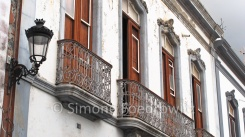 Eine weiße Häuserfassade mit braunen Holztüren und eisernen Balkonen