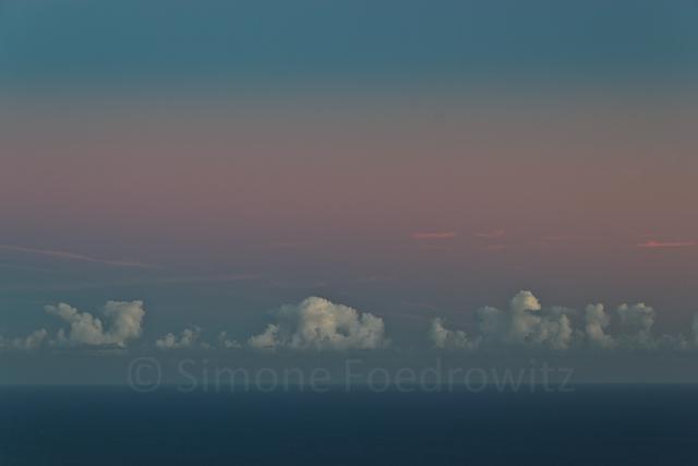 weiße Wolken am Meereshorizont nach Sonnenuntergang