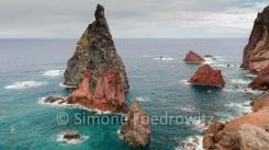 rot-schwarze Felsen ragen aus dem blauen Meer