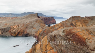 rot-orange Felsnase aus Lavagestein im Meer