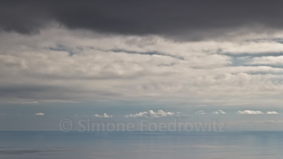 dunkle und weiße Regenwolken am blauen Meereshorizont