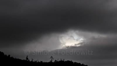 ein weißes Wolkenloch inmitten des schwarzen Himmels
