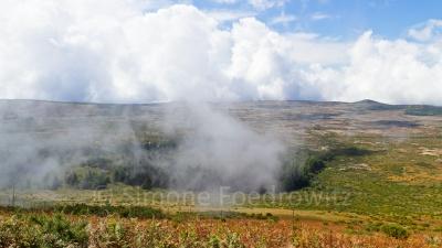 Wolken ziehen über die grün-gelbe Hochebene
