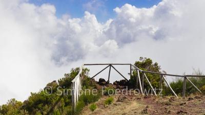 Mit Holzstangen gesicherter Bergausblick auf weiße Wolken