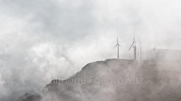 Windräder im Wolkennebel auf einem Berg