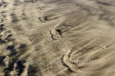 Fußspuren im marmorierten Sand