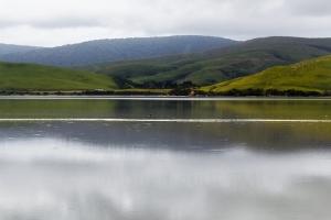 grüne Berge, die sich im Wasser spiegeln