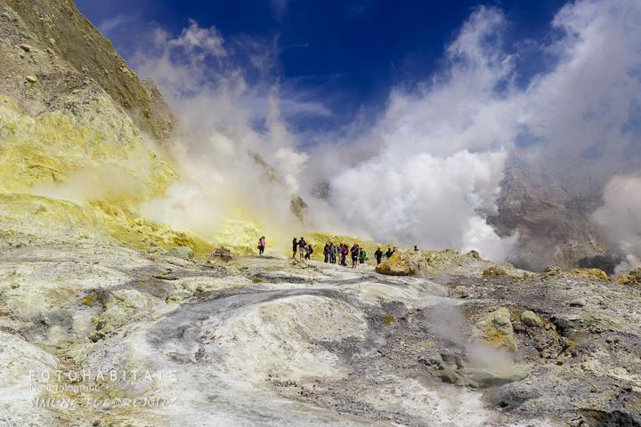 Gruppe von Menschen vor weiß dampfenden Fumarolen und Lavasee
