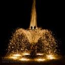 illuminierte Fontaine mit zwei Männern im Licht