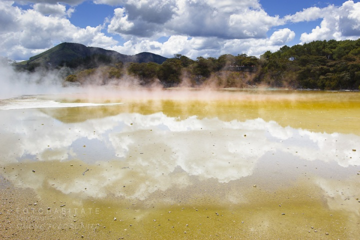 aufsteigender Dampf über gelber Fläche mit Wolkenspiegelung