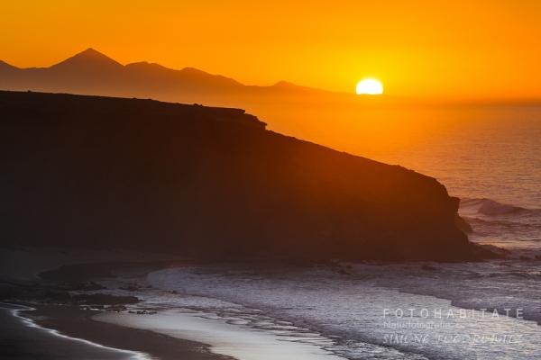glutoranger Sonnenuntergang hinter Bergen am Meer