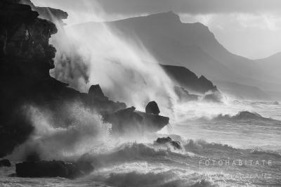 hohe Wellen an Felsklippen in schwarzweiß