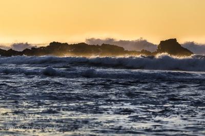 weiße Schaumkronen von Wellen vor orangem Himmel