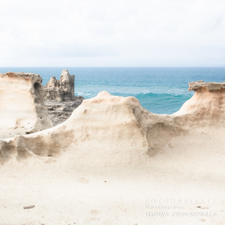 weißorange Felsen vor Meer