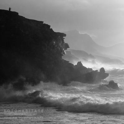 Mann auf Felsklippe bei stürmischer See
