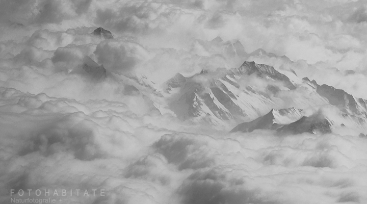 Bergspitzen im grauen Wolkenmeer