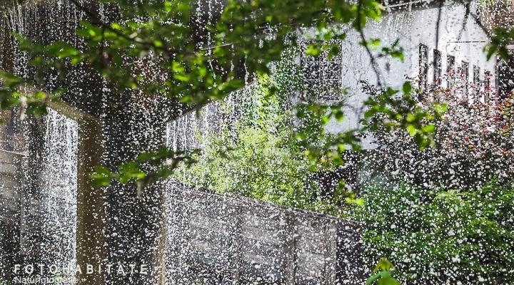 viele Wassertropfen fallen vor einem Haus hinab