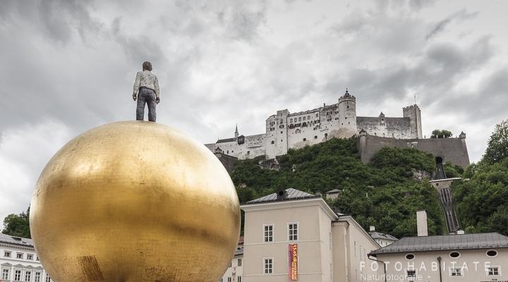 Skulptur Mann auf goldener großen Kugel vor der Festung Salzburgs