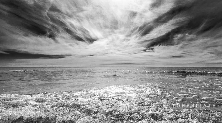 glitzernde Wellen unter dramatischem Wolkenhimmel