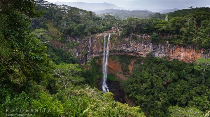 Wasserfall über gebogenen Felsen im Dschungel
