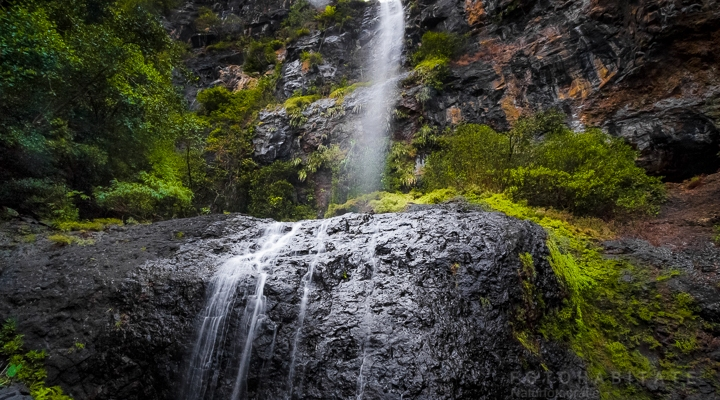 Von Felden über Steine herabfallender Wasserfall im Regenwald