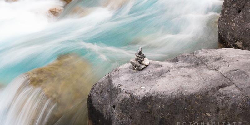 fließendes Wasser am Wegweiser aus gestapelten Steinen
