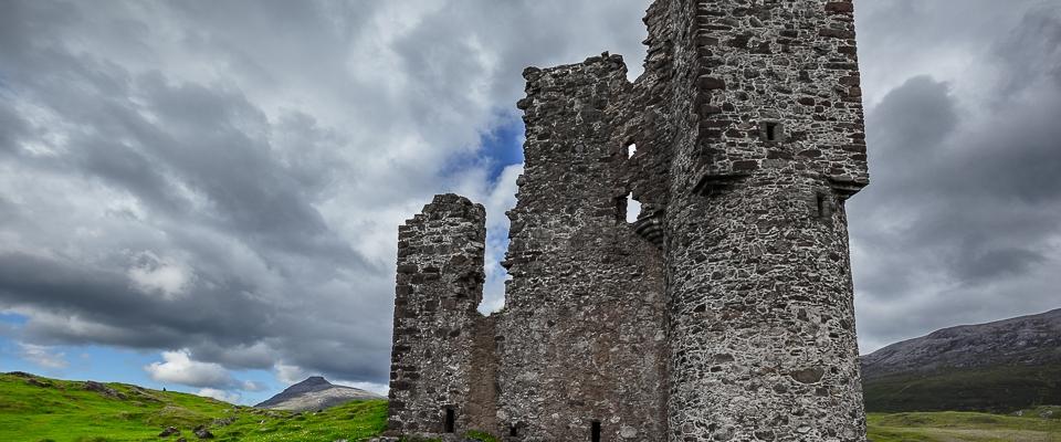 Burgruine auf grüner Wiese unter dicken Wolken