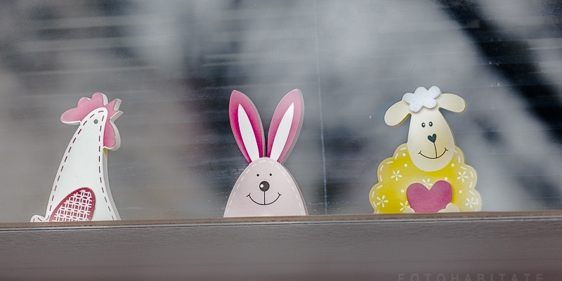 drei Figuren (Huhn, Hase, Schaf) aus Holz hinter Fensterglas