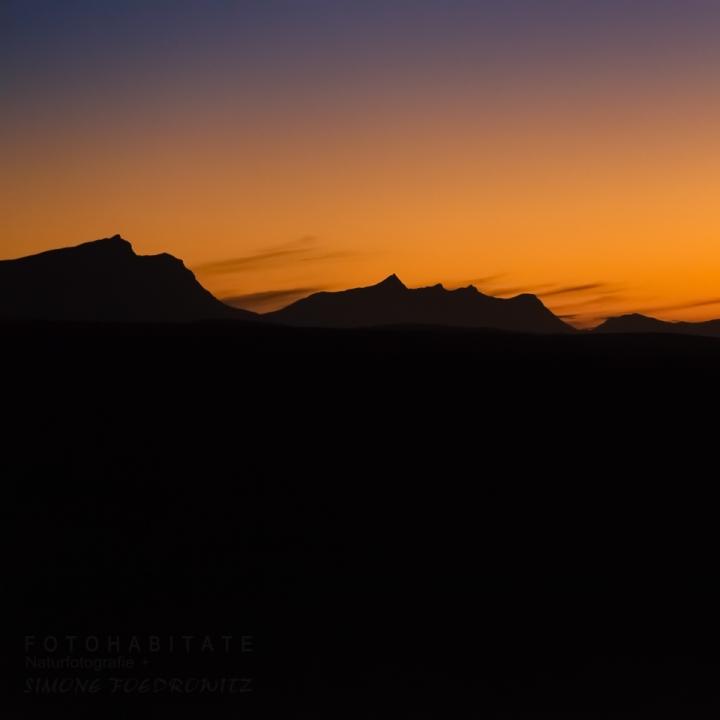 schwarze Silhouette von Bergen bei Dämmerung