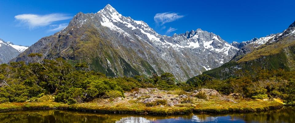 See vor schneebedeckten Berggipfeln