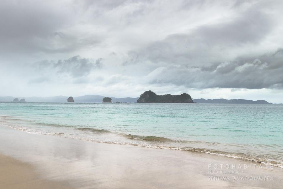 grauer wolkenverhangender Himmel über türkisem Meer